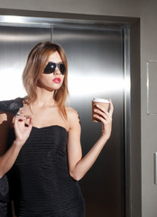 beautiful young woman in sunglasses with coffee