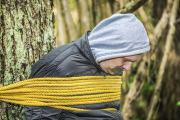 Man with tape on mouth tied to the tree