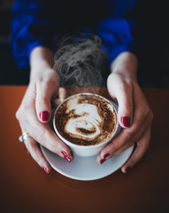 Steamming coffee in a woman's hands