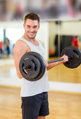 smiling man with barbell in gym