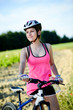 healthy young woman riding bicycle outdoor in the country