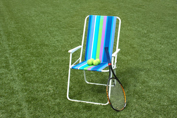 Armchair, tennis racket and four balls on court