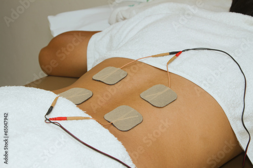 Patient  applying electrical stimulation therapy ( TENS ) on his - 65047942