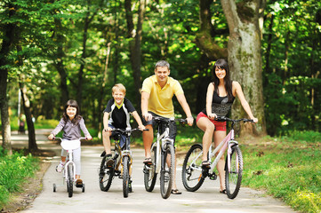 Happy family on a bicycles in the countryside