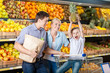 Family against shelves of fruits goes shopping