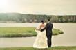 Wedding couple standing near a lake