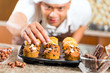 Asian man baking muffins in home kitchen