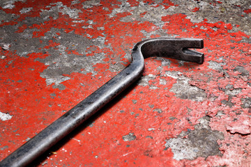 An old crowbar on a red background