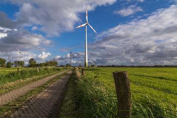 Feldweg und Windrad, blauer Himmel mit Wolken