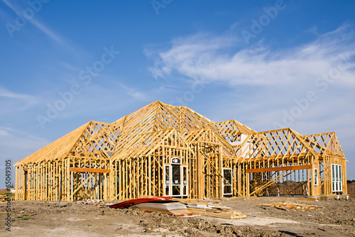 New construction home framing against blue sky - 65049305