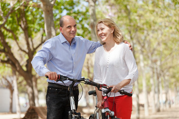 Happy couple walking with bicycles