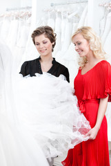 Two girls stare at the wedding dress