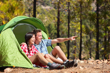 Camping couple in tent sitting looking at view