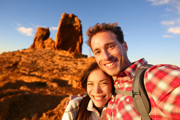 Happy couple taking selfie self portrait hiking