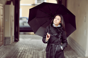 Attractive young girl with ubrella in an old town