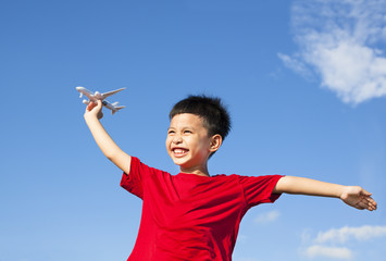 happy boy holding a airplane toy with blue sky background