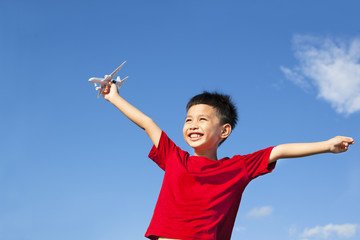 happy boy holding a airplane toy and open arms