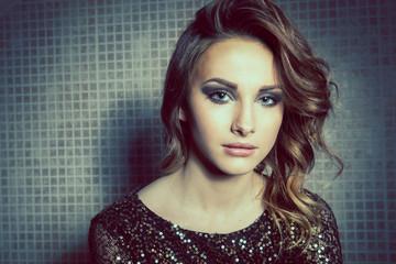 Gorgeous brunette woman with blue eyes wearing smokey eye makeup
