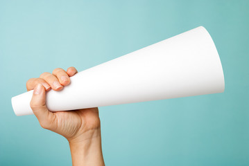Hand up holding a white blank megaphone on blue background.