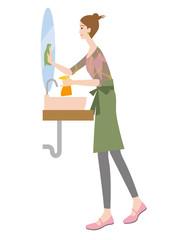 洗面所の鏡を掃除する女性