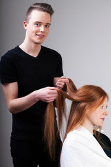 Hairdresser is combing customer hair