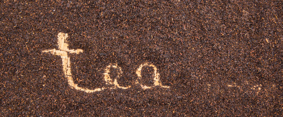 Written TEA word on dried tea leaves