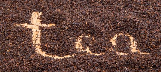 Written TEA word on dried tea leaves