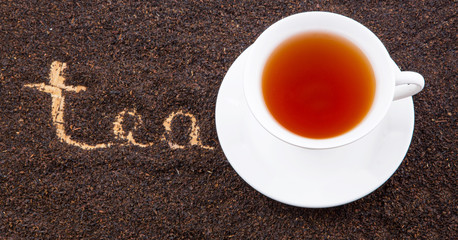 A cup of tea with the word TEA written on the dried tea leaves