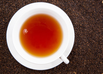 A cup of tea on dried and processed tea leaves