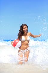 Beach woman playing with ball having fun splashing