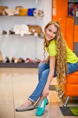 Девушка примеряет обувь в магазине