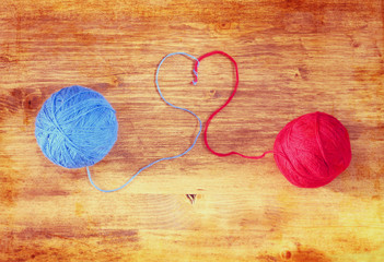 Two wool balls with heart shape over wooden board