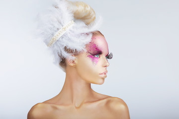 Creativity. Glamorous Fashion Model. Fancy Hair-do with Feathers
