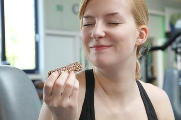 Frau isst Müsliriegel im Fitnessstudio