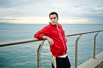 Athlete in a windbreaker stands on the pier leaning on the rail