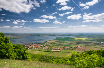 Spring countryside with village, lake, blue sky and clouds