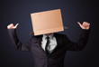 Businessman gesturing with a cardboard box on his head