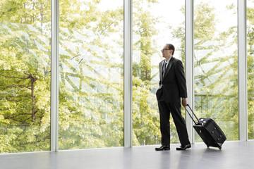 businessman in black formal wear holding trolley bag
