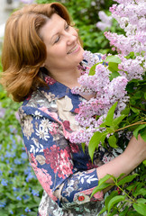 Middle-aged woman near blossoming lilac