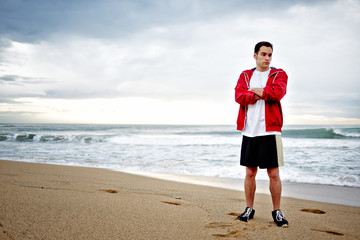 Young athlete man standing on the beach and wearily looking away