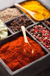 spices in box: pink  black pepper, paprika powder, curry, bay le