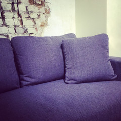 Blue textile sofa near brick wall