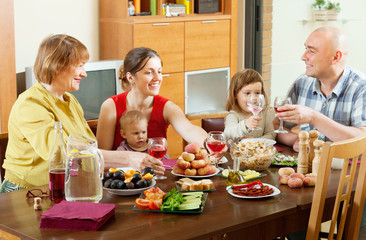 happy multigeneration family posing  over celebratory table
