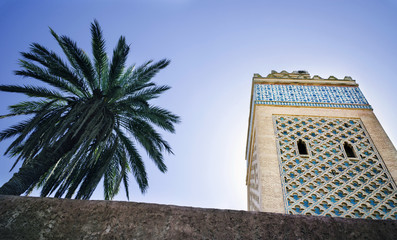 Minaret and palm tree with clear blue sky and space for copy
