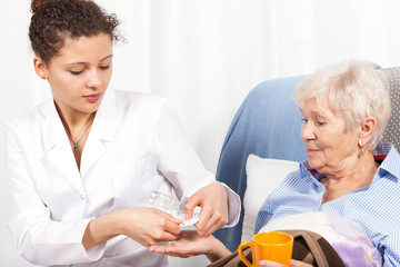 Home nurse giving elderly woman vitamin