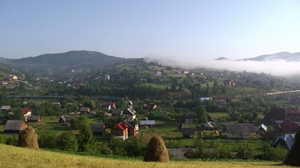 Train passing a village in Carpathians