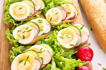 Sandwich with egg, radish and cucumber on wood background
