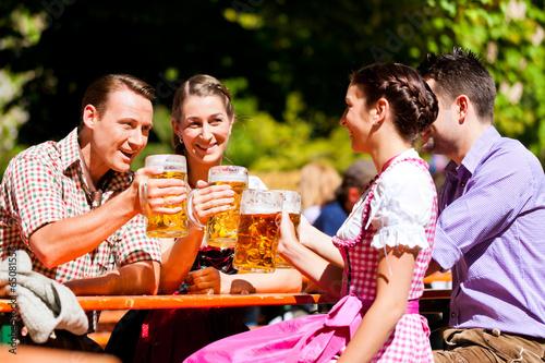 Im Biergarten - Freunde trinken Bier - 65081556