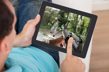 Man Playing Action Game On Digital Tablet