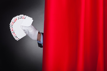 Magician Holding Fanned Cards Behind Stage Curtain